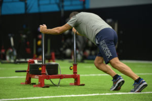 A man pushes a heavy sliding Exercise device across PFR performance indoor exercise facility